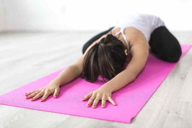 Donna che fa yoga con tappetino rosa
