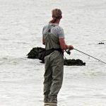 Pescatore in riva al Mare con canna da pesca